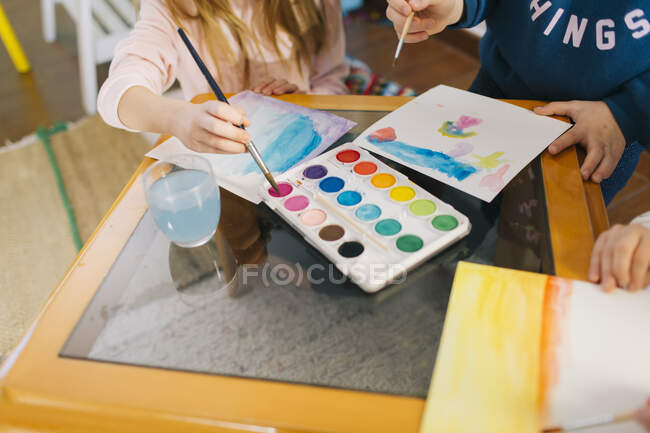 Crop cute adorable girls sitting at table with sheets of paper and watercolor while drawing pictures together — Stock Photo