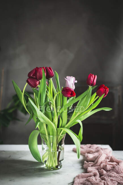 Glass vase with red tulips on the table by the window — Stock Photo
