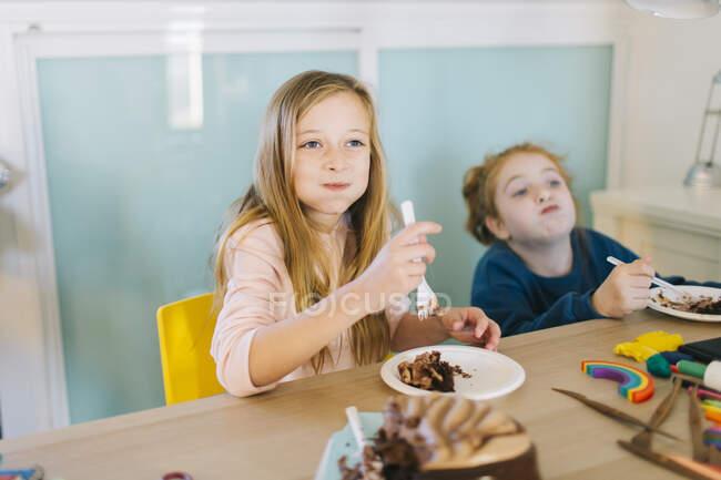 Веселі дівчатка в повсякденному одязі сидять біля столу і їдять смачний торт під час святкування дня народження. — стокове фото