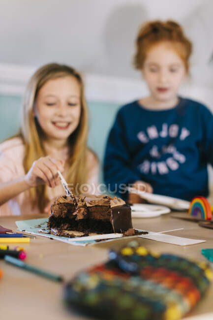 Веселі дівчатка в повсякденному одязі стоять біля столу і їдять смачний торт під час святкування дня народження. — стокове фото