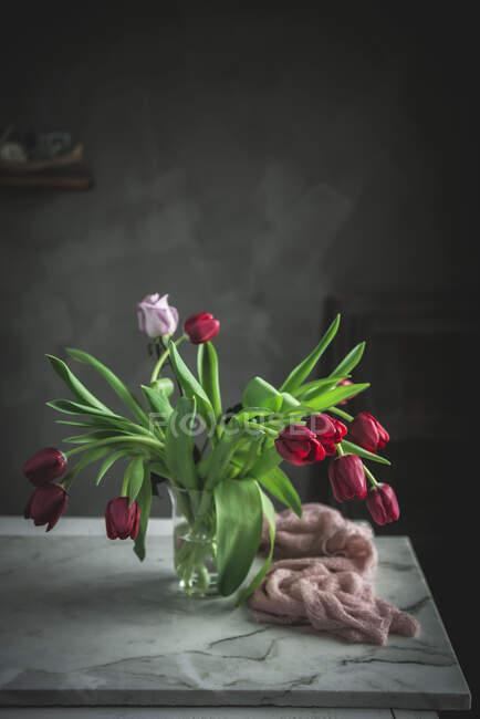 Vase en verre avec des tulipes rouges sur la table près de la fenêtre — Photo de stock