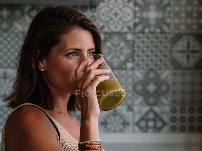 Белая девушка пьет зеленый овощной сок перед своим большим кухонным окном — стоковое фото