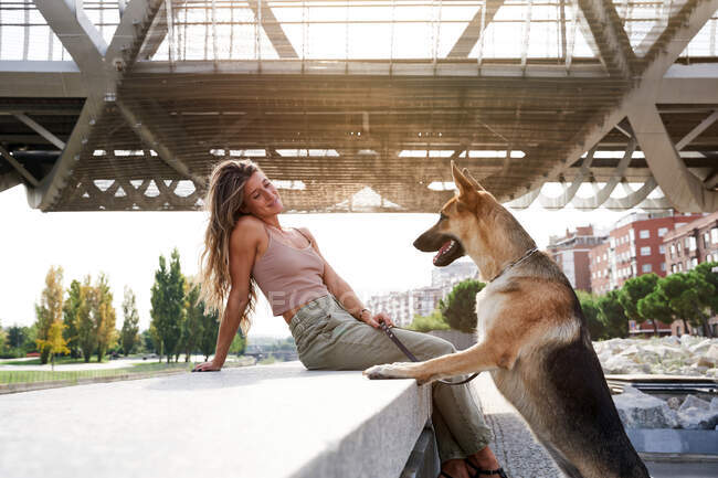 Side view of cheerful female owner leaning with German Shepherd dog on border on embankment — Stock Photo
