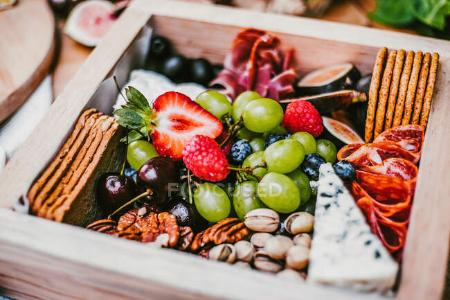 Top view of delicious fresh appetizers on wooden table near green lush shrub — Stock Photo
