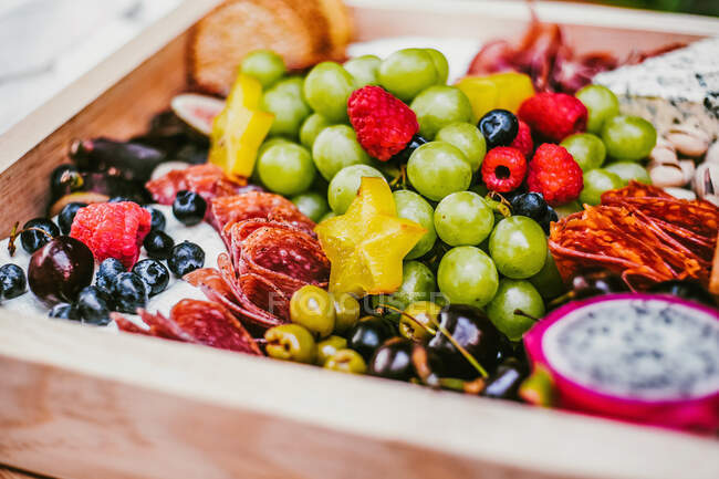 Meat delicacies near heap with fruits and berries in lumber box on table — Stock Photo