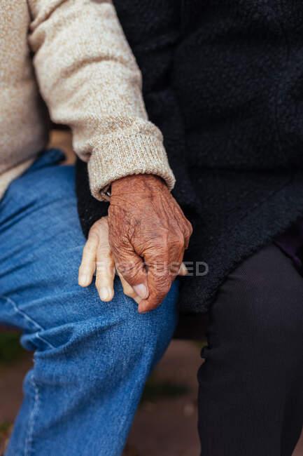 Урожай анонимной пожилой пары, держащейся за руки, сидя на скамейке в парке — стоковое фото
