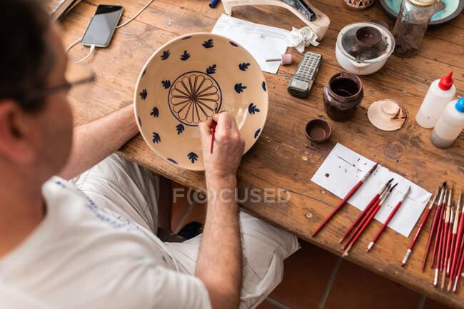 Сверху безурожайный мужчина сидит за столом с кисточками и рисует наброски на керамической тарелке ручной работы — стоковое фото