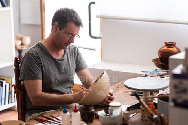 Homem sentado à mesa com escovas e desenhos em placa de cerâmica artesanal — Fotografia de Stock