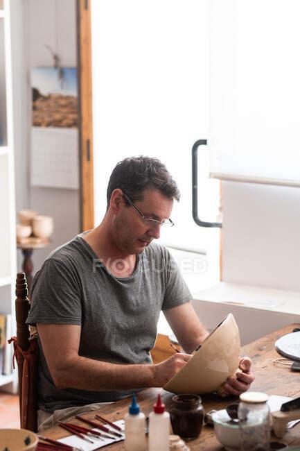 Человек сидит за столом с кисточками и рисует эскизы на ручной керамической пластины — стоковое фото