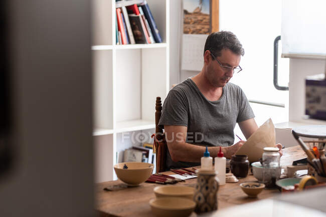 Man sitting at table with brushes and drawing sketches on handmade ceramic plate — Stock Photo