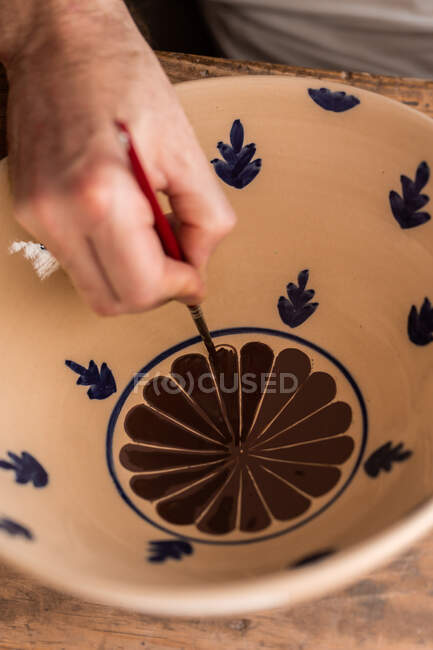 From above of crop faceless man sitting at table with brushes and drawing sketches on handmade ceramic plate — Stock Photo