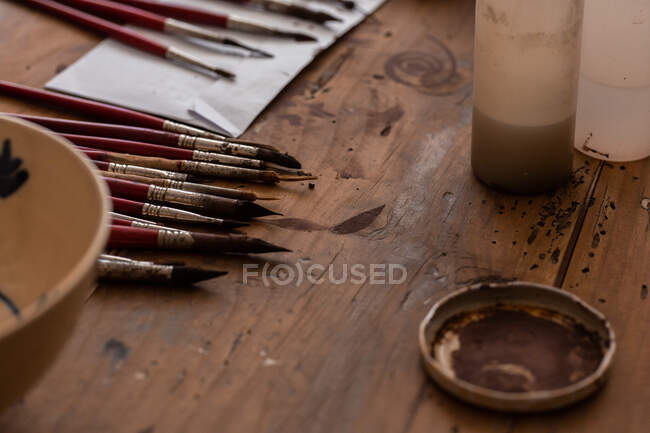 From above of various brushes near painted ceramic plate on wooden table in workshop — Stock Photo