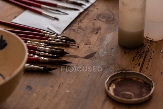 Сверху различные кисти возле окрашенной керамической плиты на деревянном столе в мастерской — стоковое фото