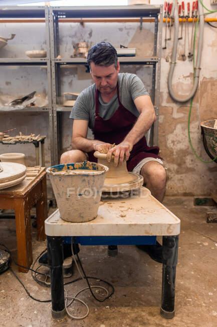 Полное тело концентрированного мастера-мужчины в фартуке сидит за столом во время скульптуры с коричневой глиной на бросающем колесе — стоковое фото