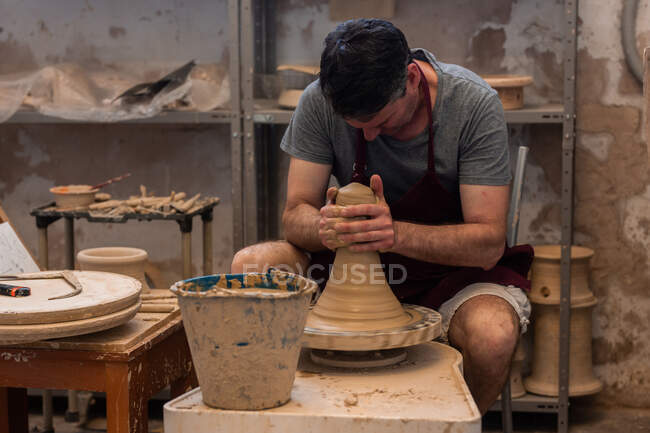 Full body of concentrated male master in apron sitting at table while sculpting with brown clay on throwing wheel — Stock Photo