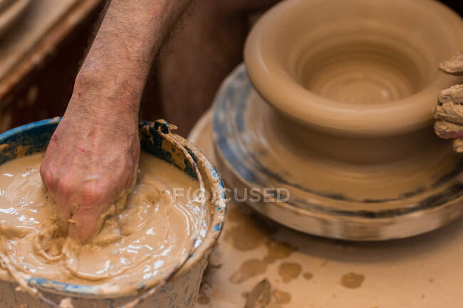 Crop unrecognizable sculptor with equipment giving shape while sculpting with brown clay on throwing wheel — Stock Photo