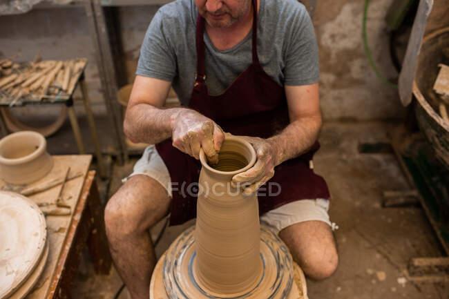 Растениеводство неузнаваемый скульптор с оборудованием придавая форму во время скульптуры с коричневой глиной на бросать колесо — стоковое фото