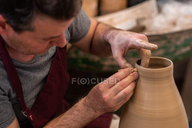 Cultivar escultor irreconhecível com equipamento dando forma ao esculpir com argila marrom na roda de lançamento — Fotografia de Stock