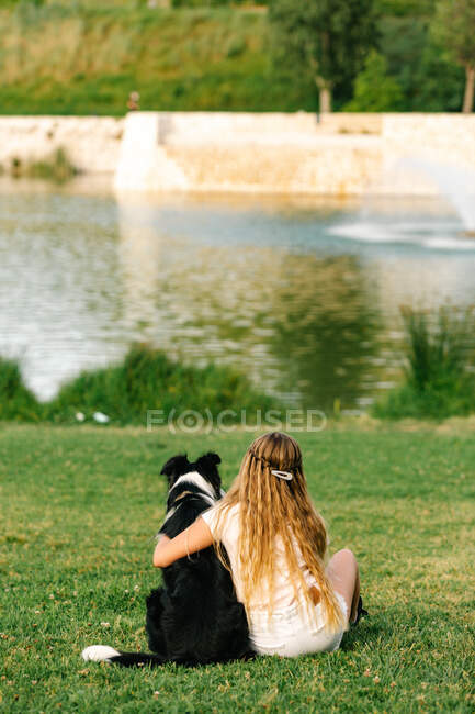 Back view of unrecognizable teenage girl embracing fluffy Border Collie dog while sitting on lawn near pond in summer park — Stock Photo