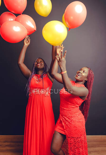 Delighted African American female friends in red dresses and with braids having fun in studio while celebrating event and tossing up air balloons — Stock Photo