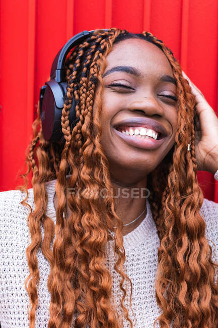 Positive African American female in wireless headphones enjoying songs with closed eyes while listening to music on street against red wall — Stock Photo