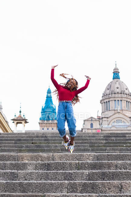 Carefree smiling African American female listening to music in headphones and jumping above stairs in city while looking at camera and showing rock gesture — Stock Photo