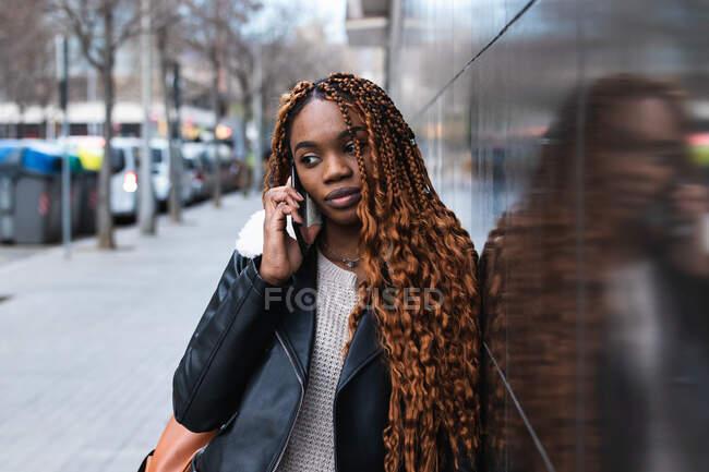 Femme afro-américaine en tenue tendance et avec des tresses appuyées sur le mur de verre du bâtiment parlant sur smartphone en ville — Photo de stock