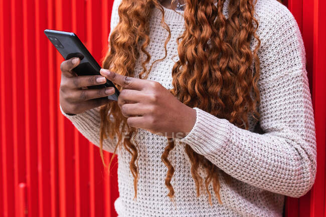 Cropped unrecognizable African American female in trendy outfit and with braids leaning on red wall of building and browsing smartphone in city — Stock Photo