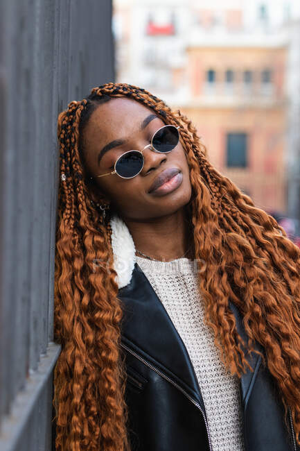 Serene dreamy African American female in stylish sunglasses and with long braids leaning on fence in city with eyes closed — Stock Photo