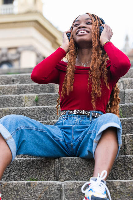 Satisfied African American stylish female sitting on stone stairs in city and enjoying music in wireless headphones looking away — Stock Photo