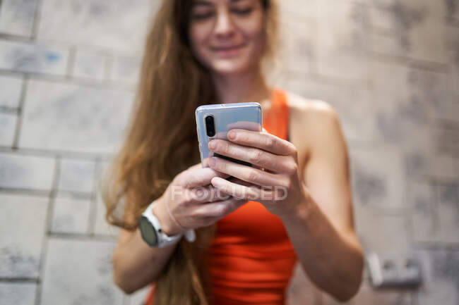 Crop anonymous female with long hair and smartwatch text messaging on mobile phone while standing in room — Stock Photo