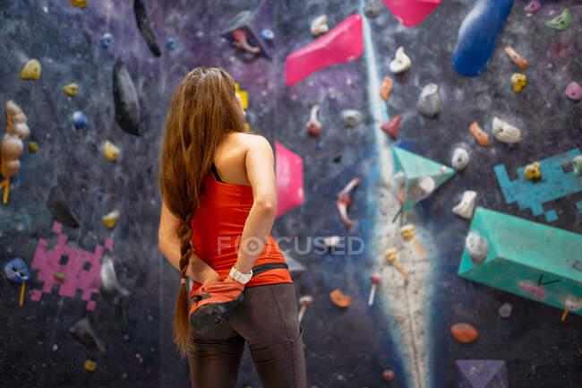 Очаровательная сильная женщина в спортивной одежде, держась за руки за спину, стоя напротив стены и глядя вверх — стоковое фото