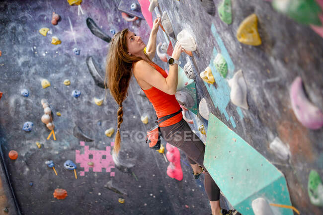 Side view of strong female athlete in sportswear clambering wall in modern bouldering center — Stock Photo