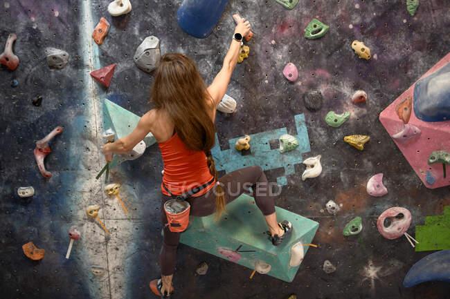 Обратный вид сильной спортсменки в карабкающейся стене в современном боулдеринговом центре — стоковое фото