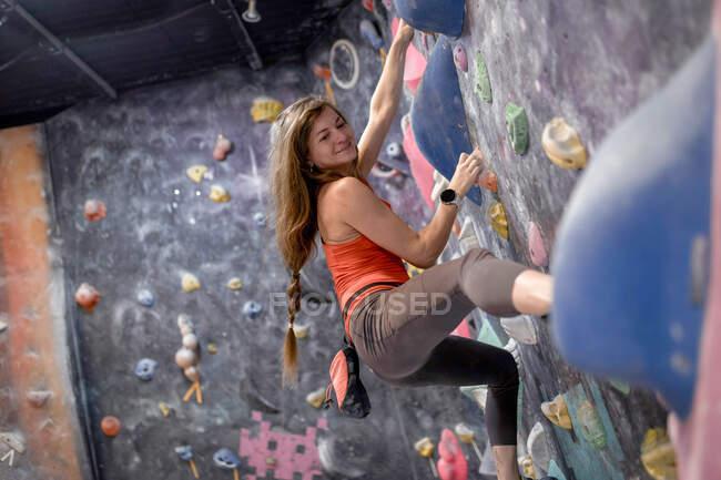 Вид сбоку на сильную спортсменку в спортивной одежде, карабкающуюся стену в современном боулдеринговом центре — стоковое фото