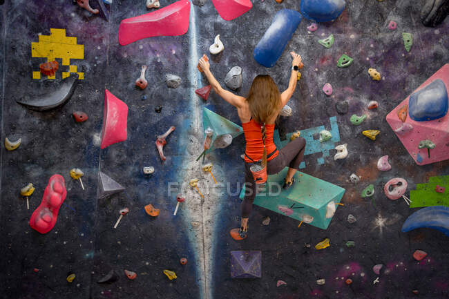 Back view of strong female athlete in sportswear clambering wall in modern bouldering center — Stock Photo