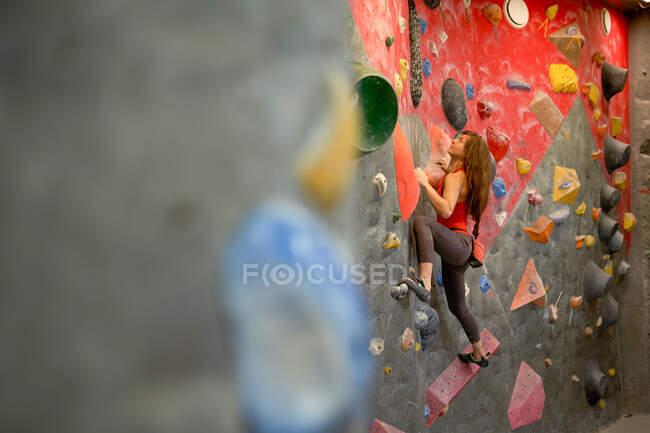 Vista laterale di forte atleta donna in abbigliamento sportivo muro aggrovigliamento nel moderno centro di boulder — Foto stock