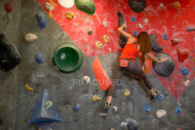Vista posteriore di forte atleta donna in abbigliamento sportivo muro aggrovigliamento nel moderno centro di boulder — Foto stock