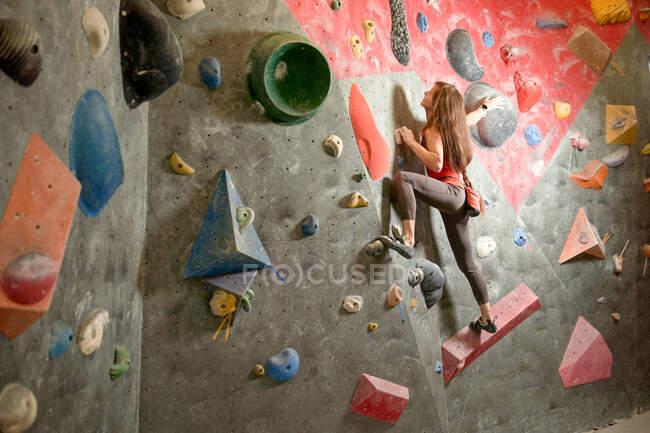 Vue latérale de l'athlète féminine forte dans le mur d'escalade de vêtements de sport dans le centre de bloc moderne — Photo de stock