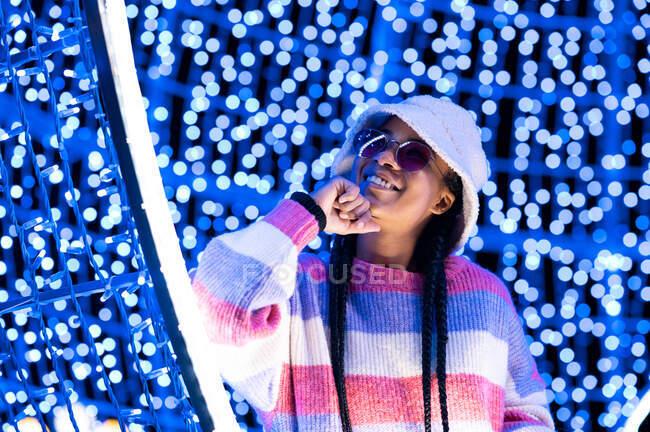 Возбужденная привлекательная афроамериканка в модной одежде смотрит в сторону, стоя в темной студии, украшенной светящимися гирляндами — стоковое фото