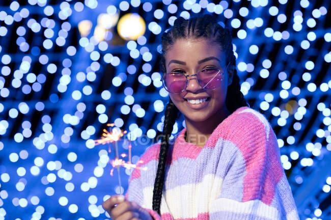 Felice giovane donna afroamericana in occhiali da sole alla moda in maglione caldo tenendo accese le luci del Bengala e guardando la fotocamera con sorriso mentre in piedi contro ghirlande incandescenti sfocate — Foto stock