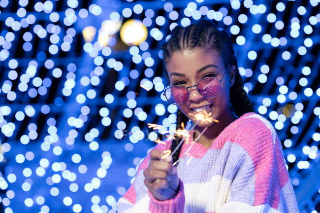 Happy young African American female in trendy sunglasses in warm sweater holding burning Bengal lights and looking at camera with smile while standing against blurred glowing garlands — Stock Photo
