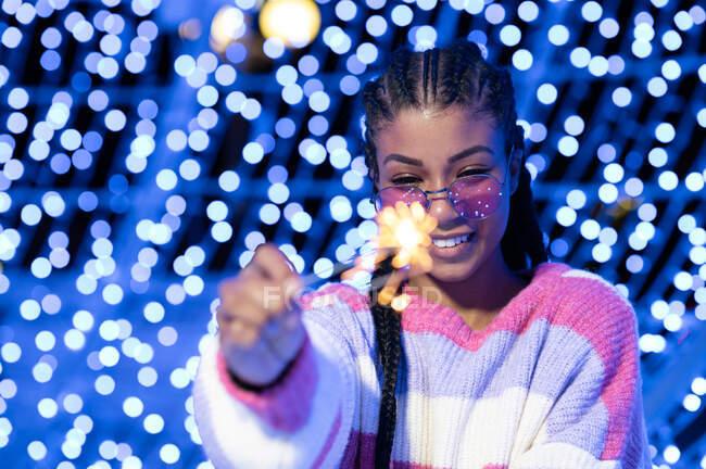 Щаслива молода афроамериканська жінка в модних сонцезахисних окулярах в теплому светрі, тримаючи Бенгальські вогні і дивлячись вниз з посмішкою, стоячи проти розмитих сяючих садів. — стокове фото
