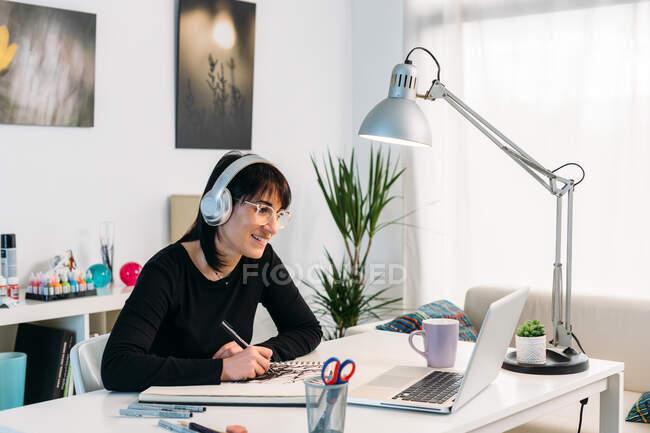 Sonriente artista femenina dibujando en cuaderno de bocetos mientras está sentada en la mesa con auriculares y viendo clases en línea en netbook en casa - foto de stock