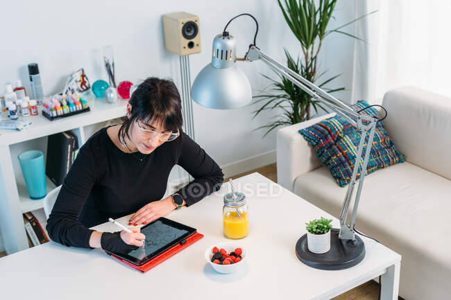 High angle of focused female designer sitting at table at home and drawing on tablet while working on creative project — Stock Photo