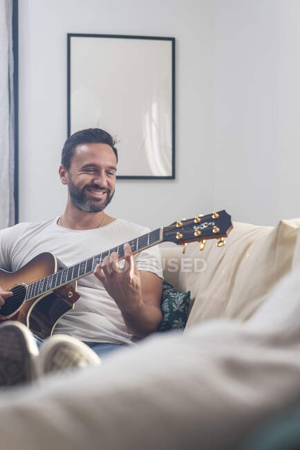 Happy adult ethnic male musician in casual clothes relaxing on comfortable sofa and playing acoustic guitar at home — Stock Photo