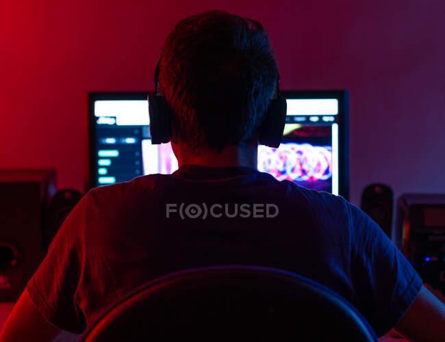 Rückansicht der ruhigen jungen Brunet in Freizeitkleidung und drahtlosem Headset surft zeitgenössischen Computer mit leerem Bildschirm, während sie am Tisch im dunklen Raum sitzen — Stockfoto