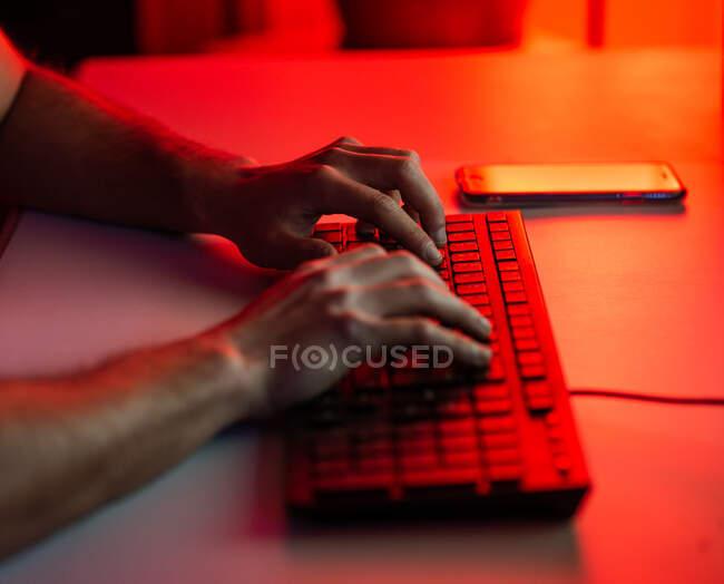 Recorte de escritura masculina anónima en el teclado mientras se trabaja en el ordenador y sentado en el escritorio con el teléfono inteligente en la habitación oscura - foto de stock