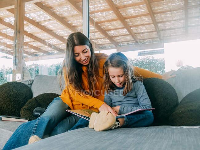 Содержание женщины подросток указывая пальцем на страницу учебника, в то время как проводить время с братом на диване дома — стоковое фото