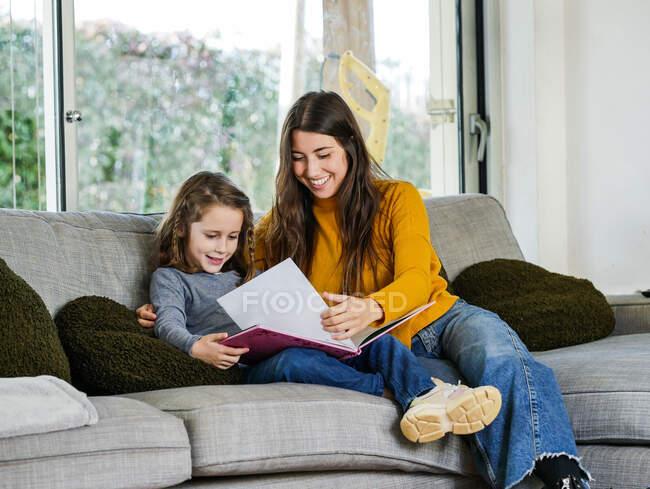 Содержание девушки подросток глядя на страницу учебника, в то время как проводить время с братом на диване дома — стоковое фото